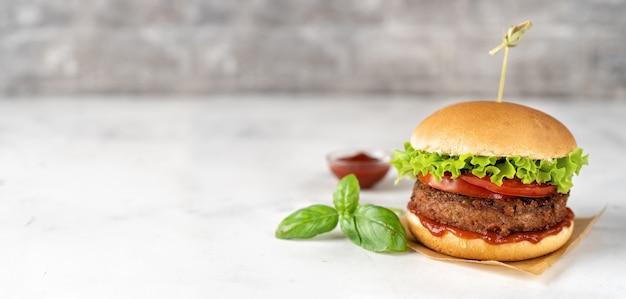 Burger végétalien fait maison sur une surface rustique blanche
