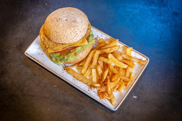 Burger végétalien avec guacamole et frites sur une plaque blanche sur fond noir