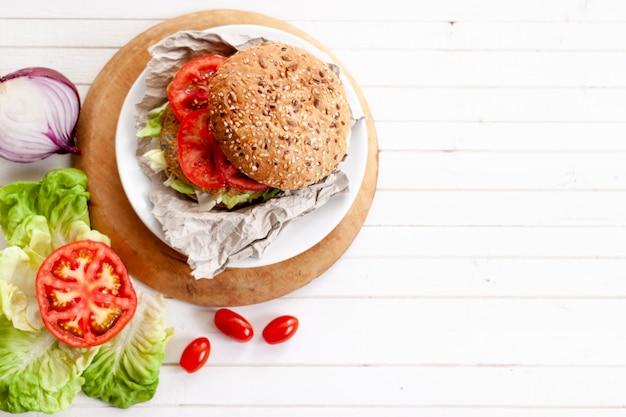Burger végétarien au quinoa avec tomate, pain burger, bol de quinoa, oignon, laitue