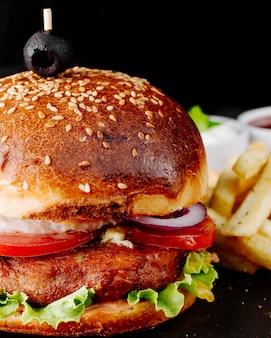Burger à la viande et aux légumes en pain brioche.