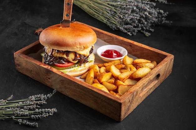 Burger de viande de boeuf avec frites et ketchup sur la planche de bois