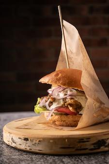 Burger de viande juteuse avec légumes frais et épices. brioche parfumée et sauces naturelles. vue de côté. sur fond sombre, pour les menus et les publicités