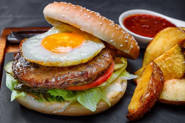 Burger avec viande et oeufs, sur une planche avec sauce et pommes de terre