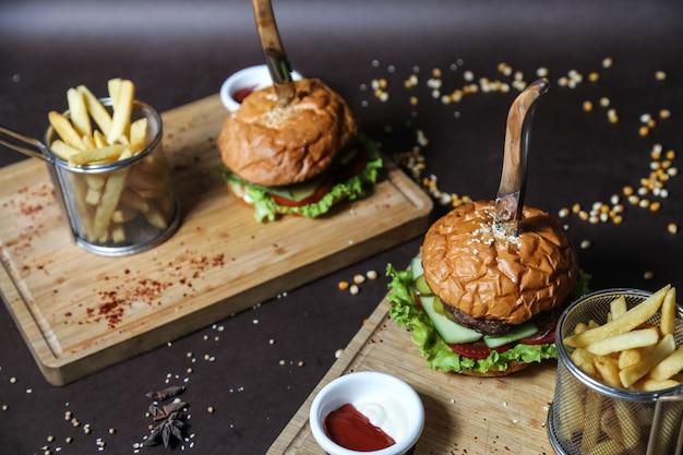 Burger de viande sur la planche de bois laitue tomate concombre frites vue latérale