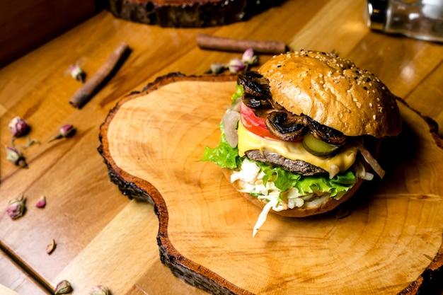 Burger de viande sur planche de bois salade de chou concombre champignons tomate fromage vue latérale