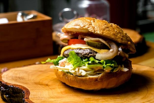Burger de viande tomate oignon salade de chou concombre vue latérale