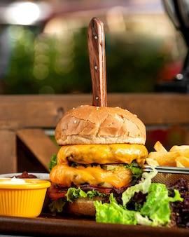 Burger de viande vue latérale avec un couteau coincé avec des frites et des soupes sur le plateau