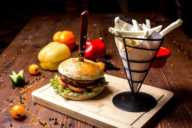 Burger de viande vue latérale avec frites sur une planche et poivron
