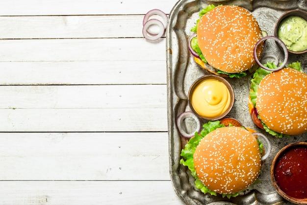 Burgers au boeuf et légumes sur un plateau en acier sur un fond en bois blanc
