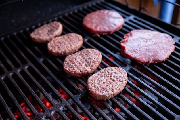 Burgers de boeuf cru avec une pincée de sel et de poivre noir sur le gril viande préparée pour griller des côtelettes de hamburger crus délicieuses galettes rondes de viande hachée crue rôtie sur une grille métallique