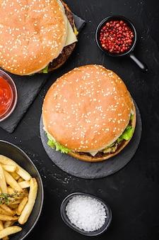 Burgers de boeuf sur fond texturé noir, vue de dessus.