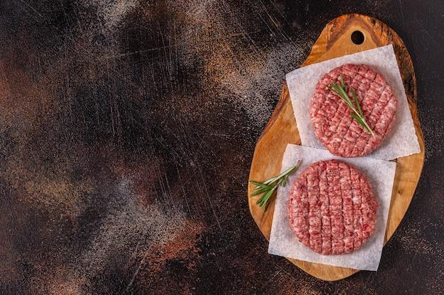 Burgers de boeuf grillés faits maison hachés crus frais sur une planche à découper en bois, vue de dessus