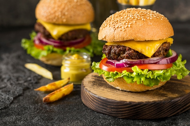 Burgers de boeuf gros plan sur une planche à découper avec sauce