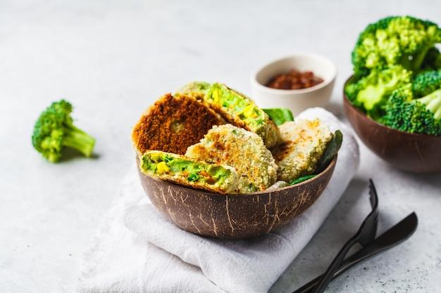 Burgers de brocoli vert dans un plat de coquille de noix de coco sur fond blanc.