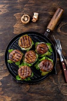 Burgers de champignons portobello grillés sur une poêle en bois en fonte, vue de dessus