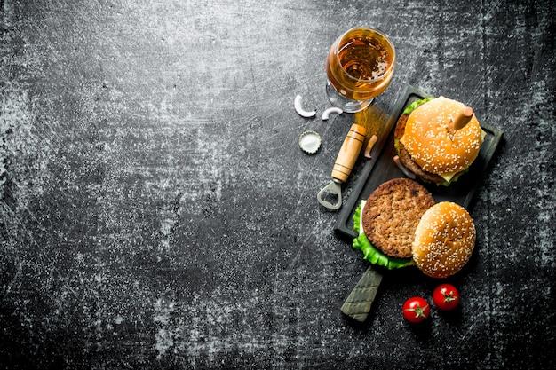 Burgers avec un couteau et de la bière dans un verre sur une table rustique noire.