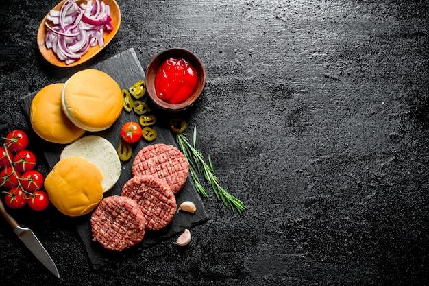 Burgers crus avec tomates, scones, sauce et oignon haché. sur fond rustique noir