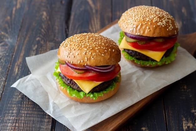 Burgers avec escalope, tomate, laitue, concombre, oignon et fromage. cuisine américaine. fast food. cheeseburger.