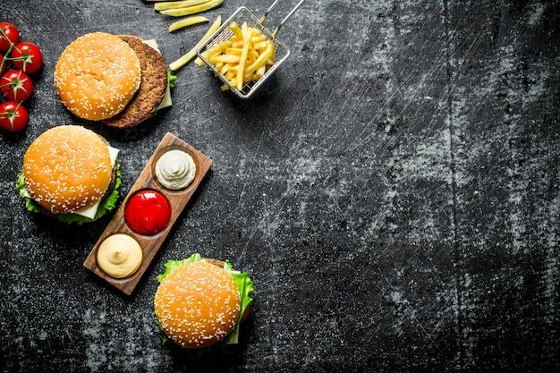 Burgers avec frites, tomates et différentes sauces. sur fond rustique noir