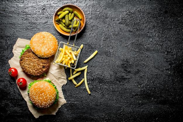 Burgers sur papier avec frites, cornichons et tomates sur table rustique