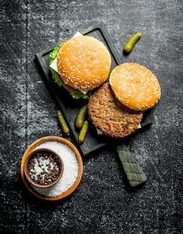 Burgers sur la planche à découper et épices dans le bol. sur fond rustique