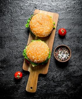 Burgers avec sel et poivre dans un bol. sur fond rustique noir