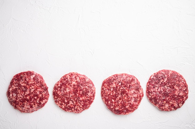 Burgers de steak haché cru de viande de boeuf, sur fond de pierre blanche, vue de dessus à plat, avec espace de copie pour le texte