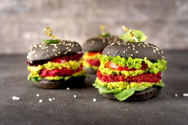 Burgers végétaliens noirs avec des galettes de betterave sur une surface sombre