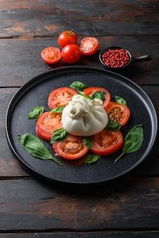 Burrata, fromage frais italien à base de crème et de lait de bufflonne ou de vache. sur plaque noire vieilles planches de table en bois.