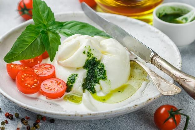 Burrata italien délicieux avec tomates cerises, pesto au basilic et huile d'olive
