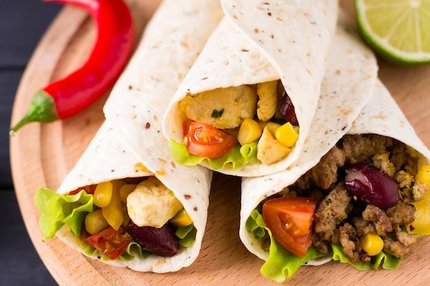 Burrito au boeuf, poulet, citron vert, poivre et légumes, sur une planche de bois.