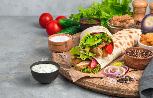 Burrito au poulet sur le mur des ingrédients sur un mur gris. vue latérale, copiez l'espace. fast food.