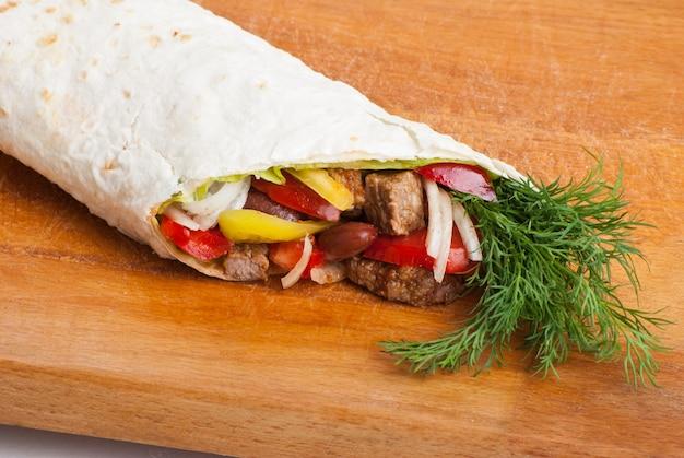 Burrito de boeuf aux poivrons jaunes et rouges, oignon et tomate sur assiette
