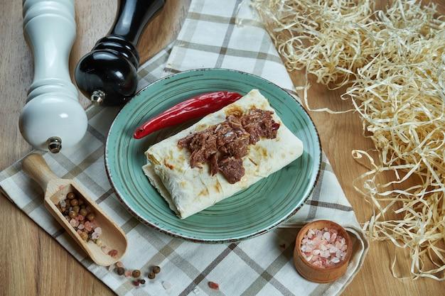 Burrito épicé ou shawarma sur une assiette bleue avec du boeuf traditionnel bouilli et doux dans une composition avec des épices. vue rapprochée. photo de nourriture. mise à plat