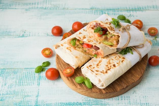 Burrito mexicain traditionnel avec des haricots et des légumes sur un espace rustique