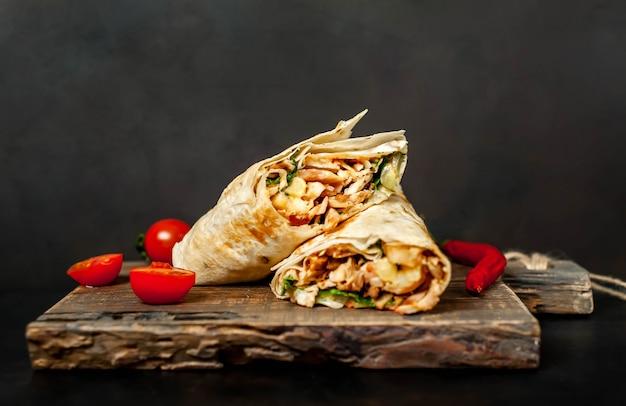 Burrito s'enroule avec du poulet et des légumes sur une planche à découper, sur un fond de béton, shawarma mexicain