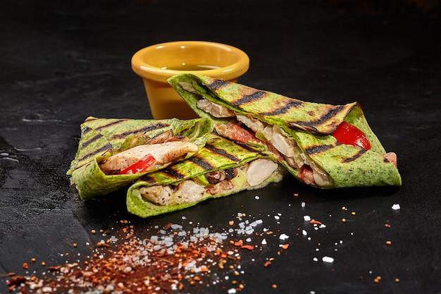 Burrito tranché dans une tortilla aux épinards avec du poulet sur une surface noire