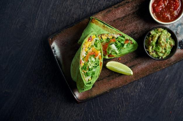 Burrito végétarien avec riz, tomates, maïs et poivron vert pita sur une plaque brune avec salsa de tomates et guacamole. rouleau de shawarma végétarien