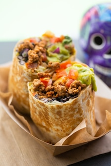 Burrito avec viande hachée et salsa et guacamole dans un café de rue de restauration rapide avec un crâne en arrière-plan