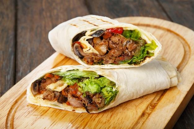 Burrito avec viande de porc et légumes au bureau en bois