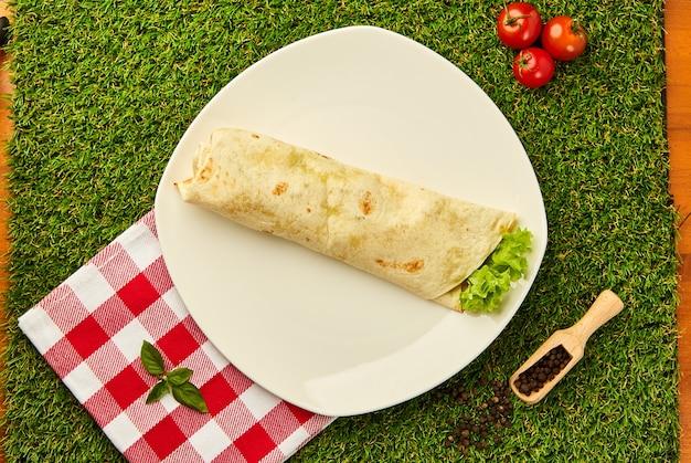 Burrito wraps au poulet et légumes sur une assiette avec de l'herbe verte, shawarma mexicain