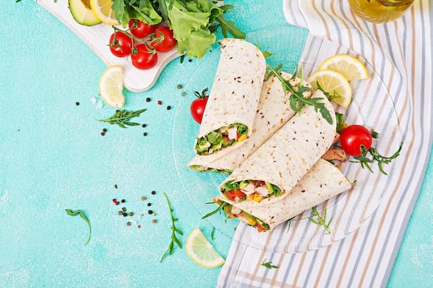 Burritos enrobé de poulet et de légumes. burrito au poulet, cuisine mexicaine. vue de dessus, pose à plat