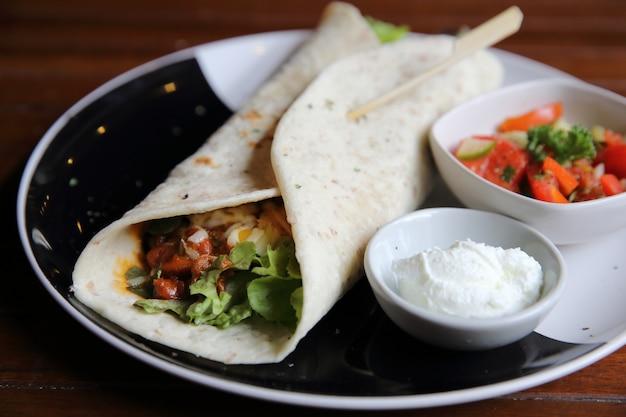 Burritos mexicains sur une assiette avec salade de tomates