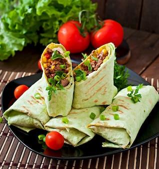 Burritos s'enroule avec du boeuf haché et des légumes sur une surface en bois