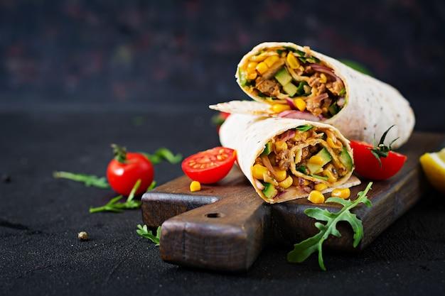 Burritos s'enroule avec du boeuf et des légumes sur fond noir. burrito de boeuf, cuisine mexicaine.