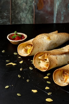Burritos savoureux au poulet et sauce dans un bol
