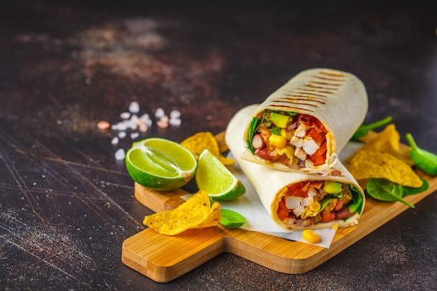 Burritos wraps avec poulet, haricots, maïs, tomates et avocat sur planche de bois