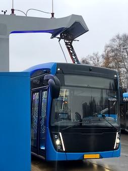 Le bus électrique bleu est chargé par pantographe à la gare