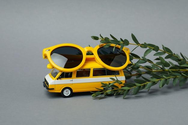 Bus jouet avec lunettes de soleil et branche sur gris