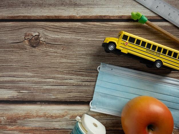 Le bus scolaire et le masque sur table en bois pour l'éducation ou le concept médical